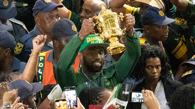 Siya Kolisi carries the Webb Ellis Cup through OR Tambo International Airport